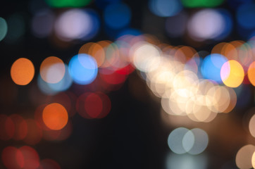 abstract blur bokeh background from cars light in dark night traffic on the road in the city for celebration merry christmas and happy new year holiday.