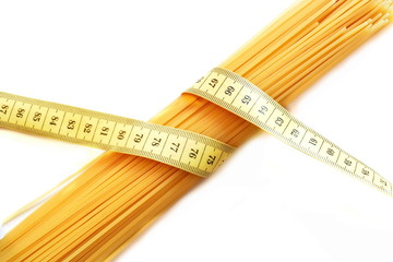 bunch of raw spaghetti wrapped in yellow measuring tape on white background