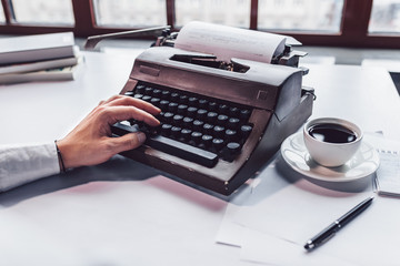 Male hand with a retro typewriter