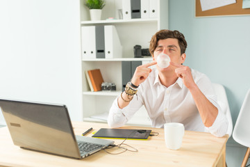 Business, fun and joke concept - young man blowing bubble of chewing gum in office