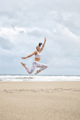 Young happy woman jumping on the beach