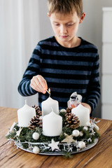 Young boy lighting the first candle on Advent Wreath on the first Sunday in December. Celebrating Christmas holidays, swiss tradition.