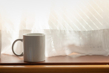 Close up of white mug cup of hot coffee on wooden table with curtain under morning sunlight.