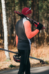 Training an athlete on the roller skaters. Biathlon ride on the roller skis with ski poles, in the helmet. Autumn workout. Roller sport. Adult man riding on skates.The athlete goes and holds sports