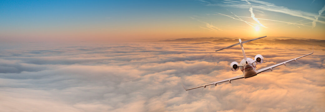 Private jet plane flying above dramatic clouds.