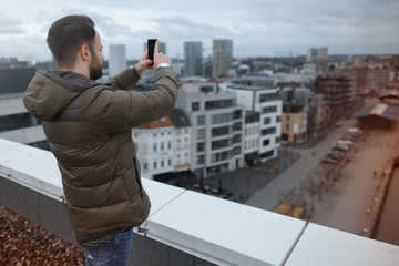 Young hipster taking pictures of the city on a smartphone from the roof of the building.