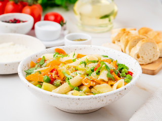 Minestrone soup, Italian cuisine. Vegetarian soup with vegetables, Penne paste, cheese. White table, side view