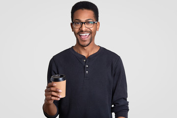 Image of happy smiling teenge boy with dark skin, wears spectacles, holds takeout coffee, enjoys fresh beverage, dressed in casual jumper, models against white background. People and coffee break