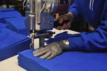 commercial textiles worker cutting a pile of fabric