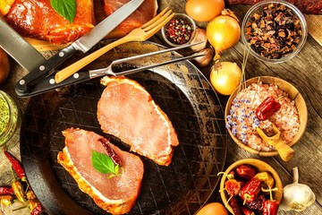 Pork chop on steel pan. Raw meat and spices. Marinated pork meat on grill. Food preparation