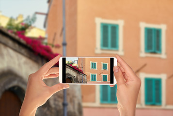 A tourist is taking a photo of street in the Trastevere area with red flowers on the roof of a building in Rome, Italy on a mobile phone