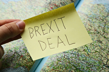 Brexit deal concept image consisting of a post it and a map in the background.