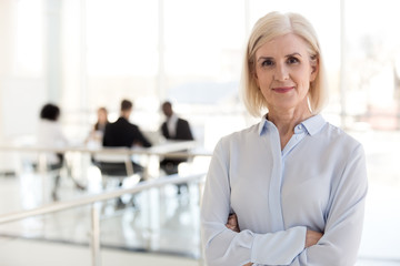 Confident mature businesswoman looking at camera, middle aged company ceo director, experienced senior female professional, old lady business coach team leader posing in office, headshot portrait