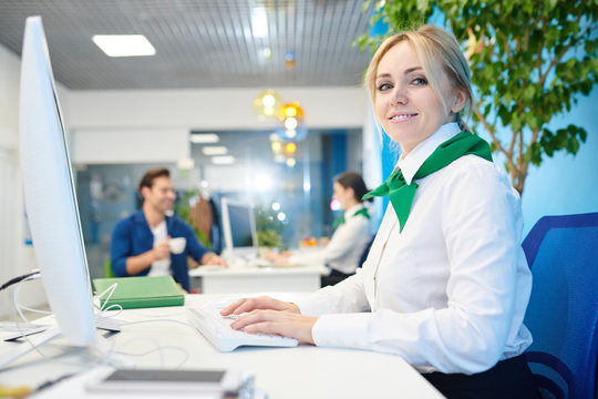 Smiling beautiful young lady wearing white blouse and neck scarf sitting at table and tying on computer keyboard while working in bank and filling online customers card.