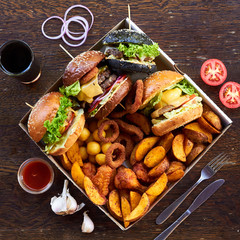On a wooden background, 4 different burgers, various hot fried foods: potatoes, balls and deep-fried rings. around the glass with a drink, sliced tomatoes, cutlery, onion rings, red sauce and garlic.