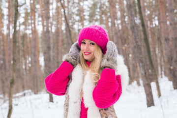 Beauty, fashion and people concept - Attractive blond woman standing in pink hat and sweaters in winter wood and smiling