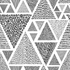 Hand-drawn triangles in doodle style seamless pattern. Black and white print for textiles. Ethnic and tribal motifs.