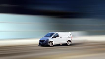 Dynamische Fahrt von einem Kleintransporter vor modernernem bewegungsunscharfen Hintergrund