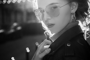 Outdoor close up monochrome, black and white portrait of young beautiful fashionable girl wearing aviator glasses, hoop earrings, turtleneck, jacket, posing in street of european city. Copy space