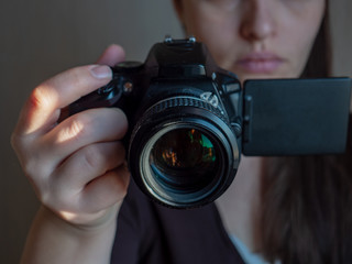 Beautiful woman with modern SLR camera of latest modification looks at folding touch screen and emotionally responds to subject of photography. Selective Focus, shallow depth of field