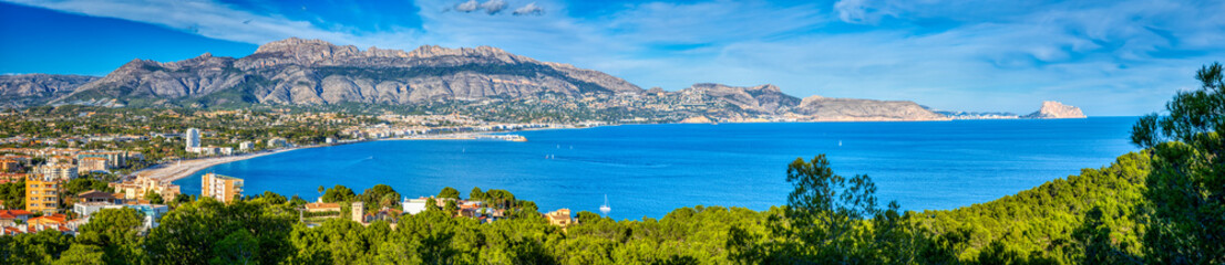 A panoramic view of Altea and the Costa Blanca from the Natural Park Serra Gelada with a bright blue ocean and sky and the mountains and towns of the surrounding area and the green trees of the park Wall mural