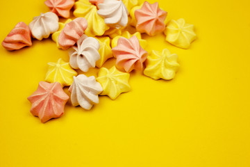 Multi-colored mini-meringues on a yellow background, top view. Place for text.