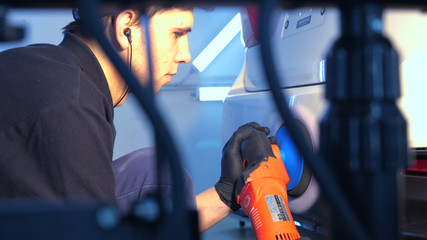 The professional guy (man) with headphones and a working uniform polishes the car body with a polishing tool. Concept from: Master class, Car Refreshment, Garage service, Special tools.