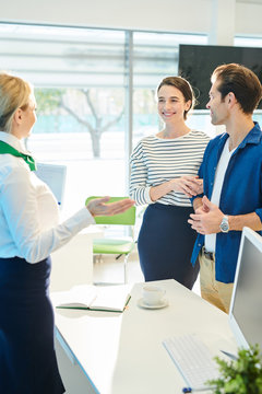 Content friendly bank representative in formalwear standing at desk with computer and open diary and gesturing hands while welcoming young couple in bank office