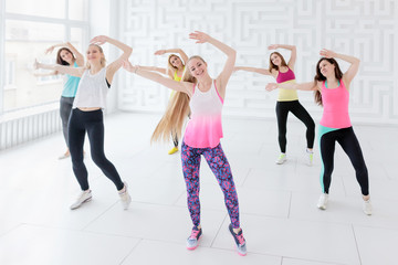 Group of young women posing with arms raised while having a fitness dance class