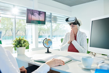 Cheerful excited senior lady in white cardigan sitting at table and keeping hands together while watching 3D video of hotel presentation with awe