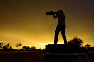 Photogrqapher with big telephoto lens in the African savannah, Moremi, Okavango delta, Africa. Orange evening on safari. Man standing on the car on the road.