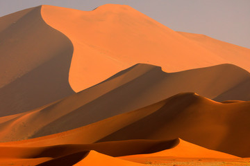 Big orange dune with blue sky and clouds, Sossusvlei, Namib desert, Namibia, Southern Africa. Red sand, biggest dun in the world. Travelling in Namibia.