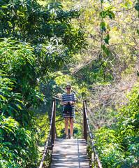 Frau auf Hängebrücke im Regenwald