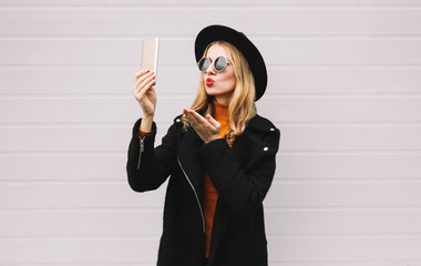 Fashion, technology and people concept - happy beautiful woman taking selfie picture by smartphone, elegant female model blowing red lips sends an air kiss posing in city on gray wall background