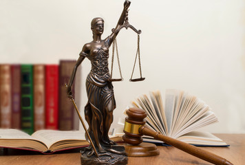 statue of justice, judge's hammer behind books on a wooden table