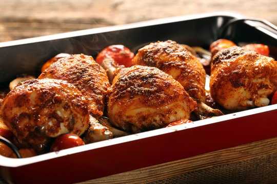 Roasted chicken drumstick with potatoes and salad on wooden background