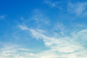 White cirrus clouds in bright blue sky (background)