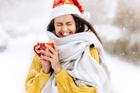 Funny dark-haired girl in a yellow sweater, a white scarf  in Santa Claus hat is standing with a red mug on a snowy street on a winter day