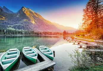 Anchored Boats on Lake Hintersee - Picturesque sunset scenery of Alpine nature in Germany, Bavaria, Europe. Autumn Landscape. Mountain peaks in backdrop, Berchtesgaden National Park, Ramsau. Wall mural