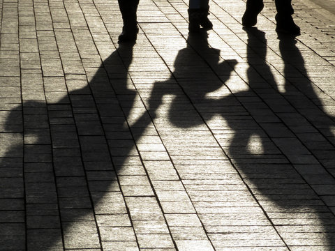 Silhouettes and shadows of parents with a child walking down the street. Man and woman holding the kid hand, concept of family, childhood, kid adoption