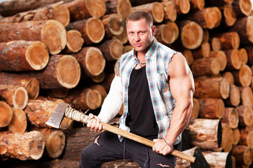 Close-up of a lumberjack worker with an ax in his hands against the background of firewood