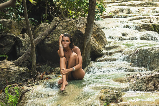 Sexy woman on the beautiful waterfall in the jungles