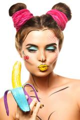 Beautiful model with creative pop art makeup holding banana