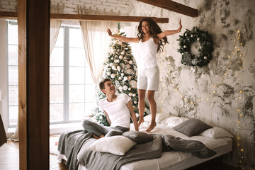 Happy girl dressed in white t-shirts and shorts is jumping on the bed next to the guy sitting there in a cozy decorated room with a New Year tree, gifts and candles