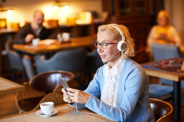 Aged blonde woman listening to music in headphones and choosing track from playlist