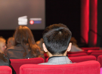 Man with a short hairstyle is sitting in a cinema chair on a blurred background of big screen and audience. It`s before a film starting. Concept: going to a cinema.