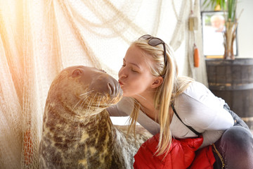 A young girl kissing a Seal in visiting centre of Marine Station of the Institute of Oceanography of the University of Gdansk in Poland