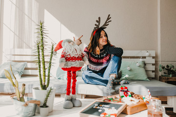 .Sweet and cheerful woman enjoying christmas at her home. Wearing christmas costume, having fun and eating tipical sweets. Lifestyle. Season photography.