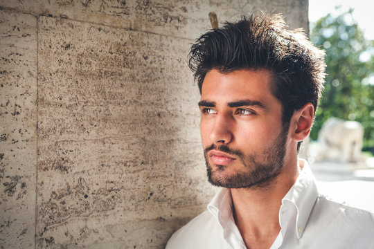 Handsome young man portrait. Intense look and eye-catching beauty. Fashionable hair and beard. The young man is wearing a white shirt.