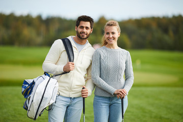 Couple of young golfers with equipment standing on large green field outdoors